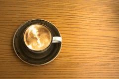 关闭一个杯子与艺术泡沫设计的热奶咖啡在一个舒适咖啡馆的一张黄色木桌上 免版税库存照片