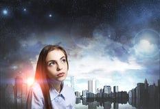 关闭一个梦想的少妇,夜城市 免版税图库摄影