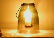 关闭一个灼烧的蜡烛被安置在n古老玻璃接收者里面 免版税图库摄影