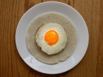 关闭一个煎蛋用在一块白色圆的板材的早餐服务的玉米蛋糕的橙色卵黄质在木表面 库存照片