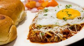 关闭一个煎蛋的射击在印地安浓小汤的用小圆面包和沙拉 免版税库存图片