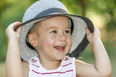 关闭一个甜矮小的微笑的男婴的画象有帽子的 免版税库存照片