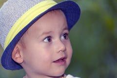 关闭一个甜矮小的微笑的男婴的画象有帽子的 库存照片