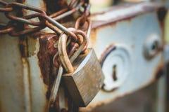 关闭一个生锈的链子的老锁围拢铁门 免版税库存照片