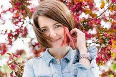 关闭一个美丽的女孩的画象有站立在一个开花的苹果庭院里的桃红色头发的 春天,户外 免版税图库摄影