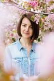 关闭一个美丽的女孩的画象有站立在一个开花的苹果庭院里的桃红色头发的 春天,户外 免版税库存图片