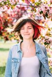 关闭一个美丽的女孩的画象有站立在一个开花的苹果庭院里的桃红色头发的 春天,户外 库存照片