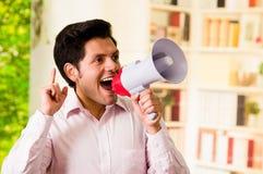 关闭一个英俊的人尖叫与一台扩音机在被弄脏的背景中 免版税图库摄影