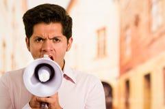 关闭一个英俊的人尖叫与一台扩音机在被弄脏的背景中 免版税库存照片
