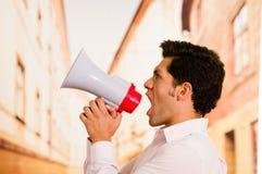 关闭一个英俊的人尖叫与一台扩音机在被弄脏的背景中 图库摄影