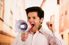 关闭一个英俊的人尖叫与扩音机,做一个信号用他的手在被弄脏的背景中 免版税库存照片