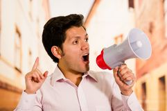 关闭一个英俊的人尖叫与扩音机,做一个信号用他的手在被弄脏的背景中 免版税库存图片