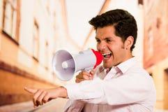关闭一个英俊的人尖叫与扩音机,指向他的手某人,在被弄脏的城市背景中 图库摄影