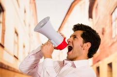关闭一个英俊的人尖叫与扩音机,指向天空在被弄脏的背景中 图库摄影