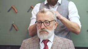 关闭一个英俊的老人的美发师s工作在理发店 股票录像