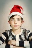 关闭一个青春期前的男孩的画象圣诞老人帽子的 库存照片