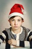 关闭一个青春期前的男孩的画象圣诞老人帽子的 库存图片