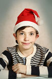 关闭一个青春期前的男孩的画象圣诞老人帽子的 图库摄影