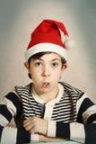 关闭一个青春期前的男孩的画象圣诞老人帽子的 免版税库存图片