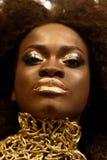 关闭一个年轻女性时装模特儿的秀丽画象与卷发和金子构成的 免版税库存图片