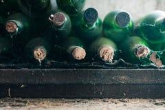 关闭一些非常老和多灰尘的酒瓶在葡萄酒库里 库存照片