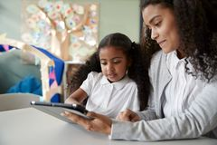 关闭一位年轻黑人女小学生在一张桌上在学会一的一间幼儿学校教室坐一个与一个女老师我们 库存照片