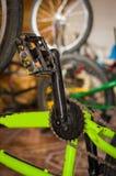 关闭一位技工固定的自行车脚蹬在一个车间,在被弄脏的背景中 免版税库存图片