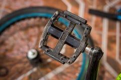 关闭一位技工固定的自行车脚蹬在一个车间,在被弄脏的背景中 库存图片