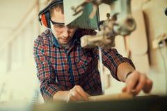 关闭一位年轻木匠在工作 他使用一把带锯 免版税图库摄影