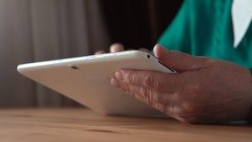 关闭一台白色片剂个人计算机在年迈的妇女手上-侧视图 库存照片