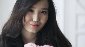 关闭一名惊人美丽的亚裔妇女嗅到的康乃馨 影视素材