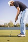关闭一名投入的高尔夫球运动员 免版税库存照片