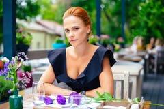 关闭一名美丽的聪明的妇女的画象有明亮的红色头发的 一件黑礼服的时髦的女孩在a.c.大阳台  免版税库存照片