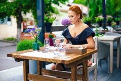 关闭一名美丽的聪明的妇女的画象有明亮的红色头发的 一件黑礼服的时髦的女孩有一杯咖啡的 免版税库存图片