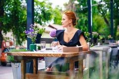 关闭一名美丽的聪明的妇女的画象有明亮的红色头发的 一件黑礼服的时髦的女孩有一杯咖啡的 免版税图库摄影