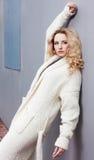关闭一名美丽的年轻白肤金发的妇女的画象一双白色外套大被编织的时尚和运动鞋 Streetstyle 免版税库存照片