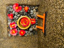 关闭一套cattleya兰花红色花和石头作为在扔石头的地面的供奉在日本 库存照片