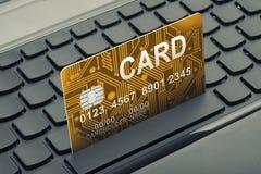 关闭一张金黄颜色信用卡的射击在键盘的作为网上购物的标志 库存照片