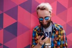 关闭一愉快的行家年轻人读一则消息在他的手机,在五颜六色的背景 免版税库存照片