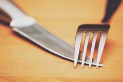 关闭一把银色刀子和叉子在一张棕色桌上 免版税库存照片