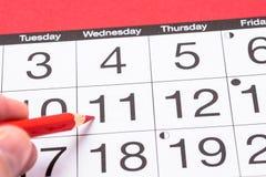 关闭一本日历用有一支红色铅笔的一只手 库存图片