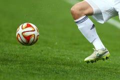 关闭一条足球运动员的腿和脚白色运行和滴下与球的袜子和浅灰色的鞋子的使用在gr 免版税库存图片
