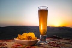 关闭一杯与快餐的啤酒在阳光背景,在草的啤酒 免版税库存图片