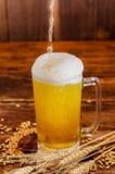关闭一杯与泡沫的低度黄啤酒,与麦子分支和麦子在一张木桌上在被弄脏的背景中 库存照片