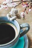 关闭一杯葡萄酒蓝色咖啡的看法与天使小雕象的和在木背景的开花的树枝 免版税库存照片