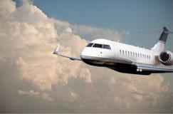 关闭一次私人喷气式飞机飞行通过多云天空 库存照片