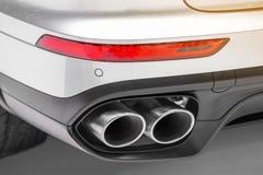 关闭一白色强有力的moder的双重镀铬物排气管 免版税库存图片