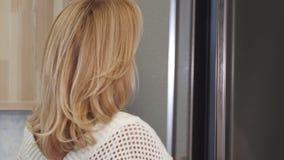 关闭一美丽的妇女微笑的看在冰箱 影视素材