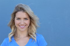 关闭一美好白肤金发女孩微笑的纵向 查出在蓝色背景 库存照片