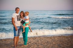 关闭一起拥抱在海滩的年轻愉快的爱恋的家庭在海洋,愉快的生活方式家庭观念附近 免版税库存图片